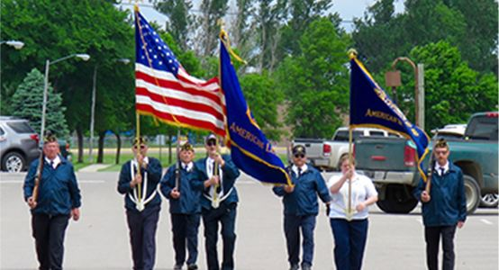 Soilders holding flags while marching in a parade
